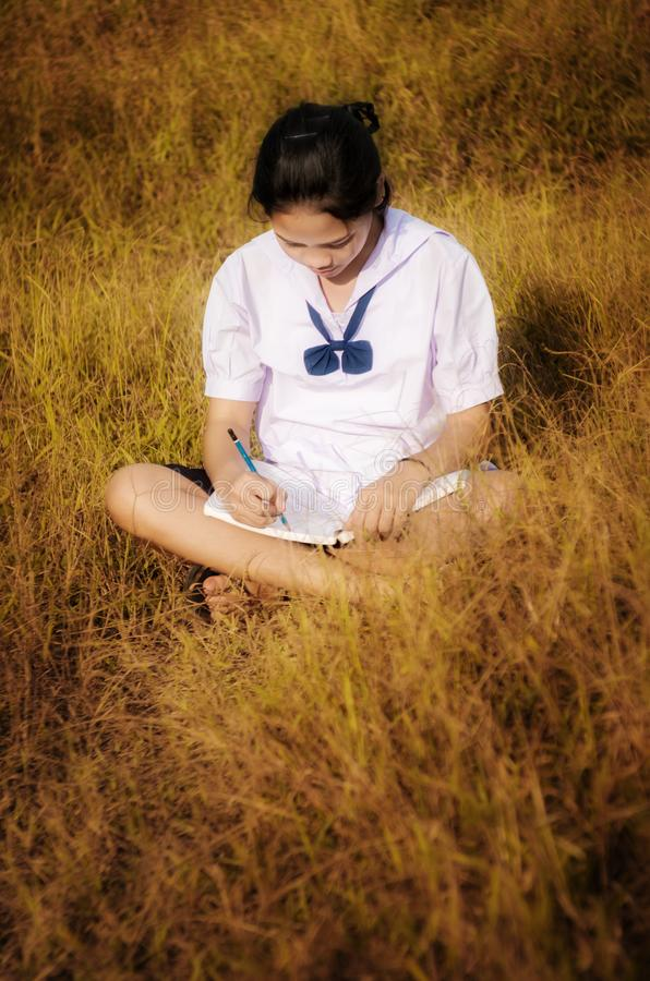 Ung flickaläsning och handstil en bok i guld- äng arkivbild