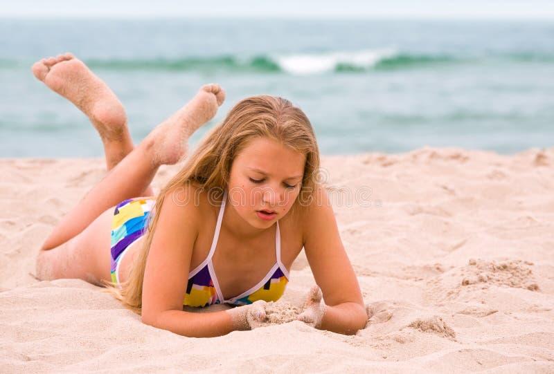Ung flickalay på stranden royaltyfri bild
