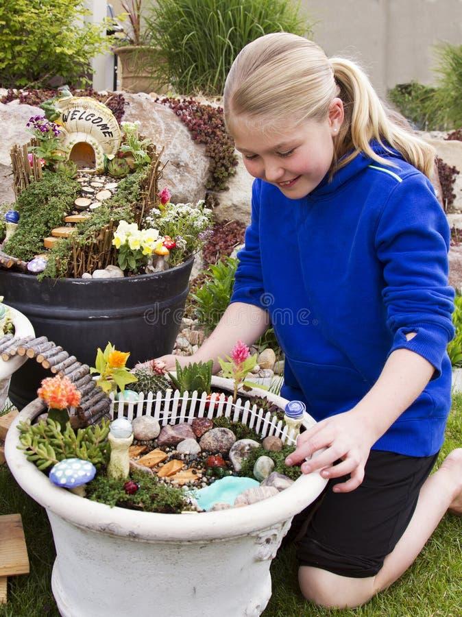 Ung flickaportion som gör fen att arbeta i trädgården i en blomkruka royaltyfri bild