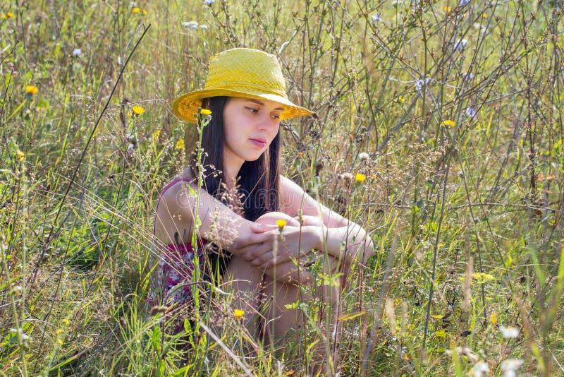 Ung flickasammanträde i gräset och om något tänker royaltyfri bild