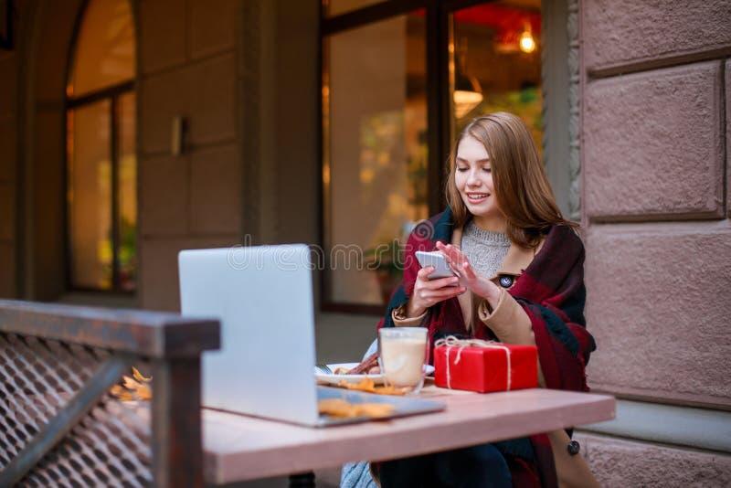 Ung flickasammanträde i kafé och användamobiltelefon utanför I hösten fotografering för bildbyråer