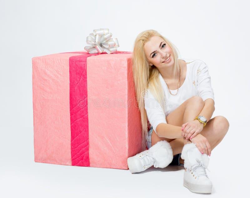 Ung flickasammanträde nära en stor gåva, på vit bakgrund royaltyfri fotografi