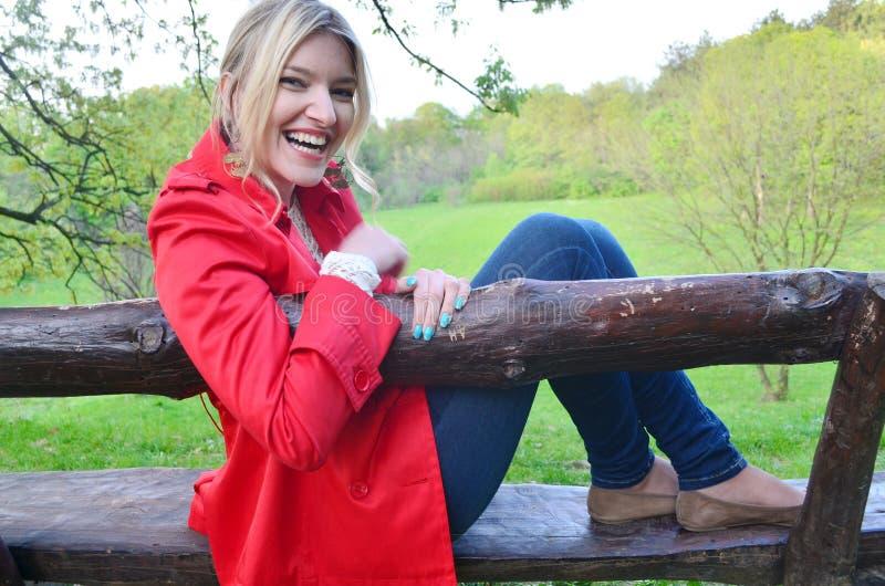 Ung flickasammanträde på bänken i parkera royaltyfria bilder