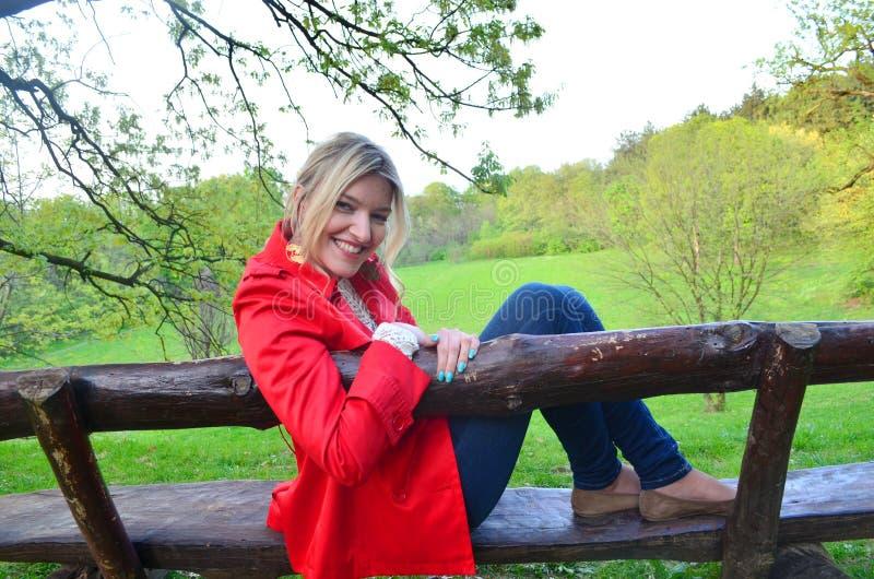 Ung flickasammanträde på bänken i parkera arkivfoton