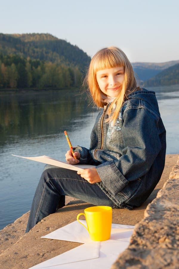 Ung flickasammanträde på en parkera arkivbilder