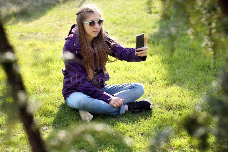Ung flickasammanträde på gräset med mobiltelefonen royaltyfri foto