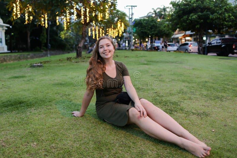 Ung flickasammanträde på gräsmatta, bärande kakier klär royaltyfri bild