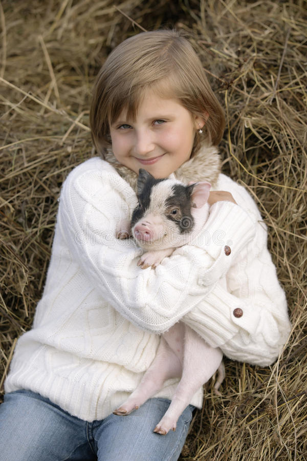 Ung flickasammanträde på hö som ler och rymmer ett svin i hans leenden Livsstilstående royaltyfri bild