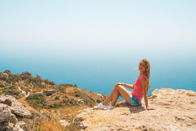 Ung flickasammanträde på kanten av klippan arkivbilder