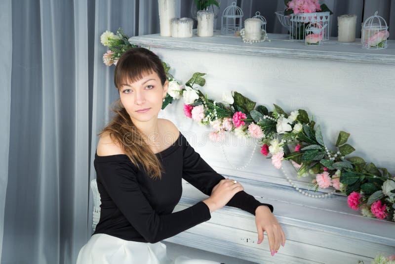 Ung flickasammanträde på pianot fotografering för bildbyråer