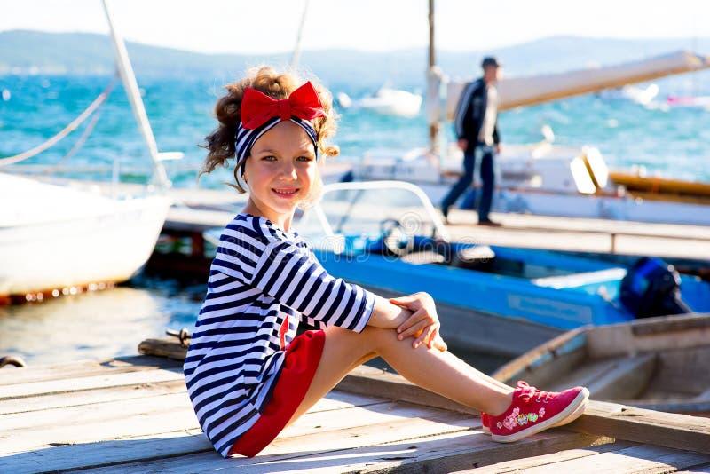 Ung flickasammanträde på skeppsdockan arkivfoto