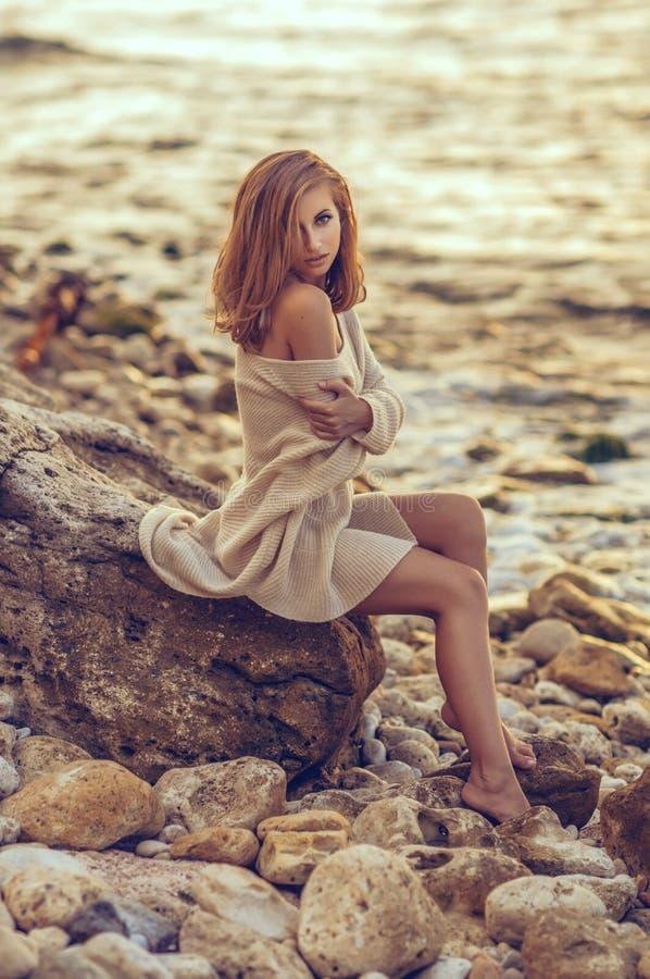 Ung flickasammanträde på stranden efter solnedgång i havsbakgrunden royaltyfria bilder