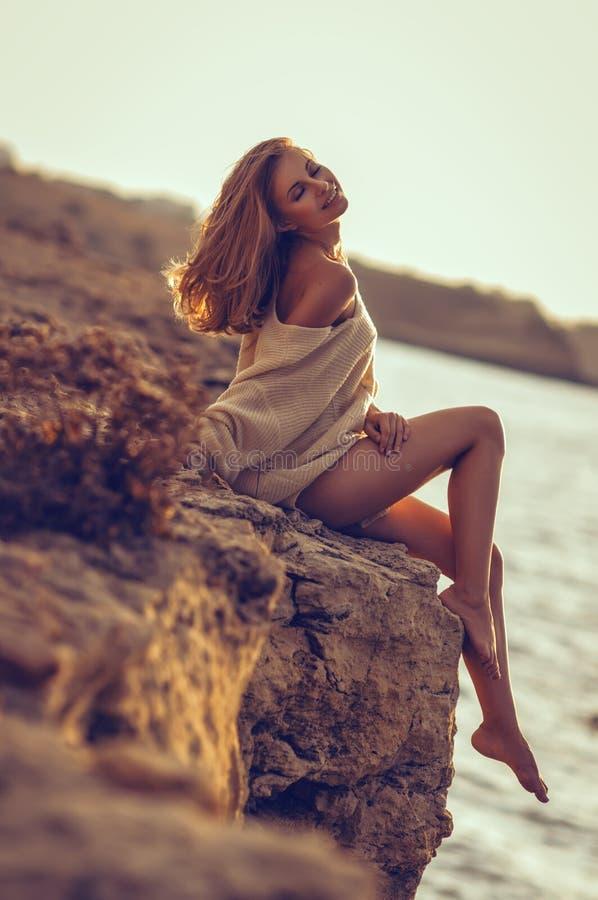 Ung flickasammanträde på stranden efter solnedgång i havsbakgrunden royaltyfri bild