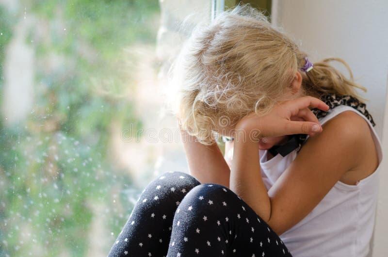 Ung flickasammanträde vid fönstret och gråt arkivfoto