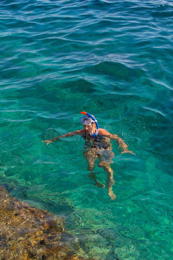 Ung flickasimning i havet royaltyfria bilder