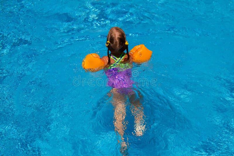 Ung flickasimning i pölen Idyllisk ferie royaltyfria foton