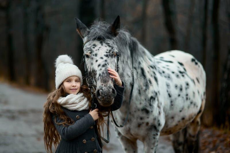 Ung flickastående med Appaloosahästen och Dalmatianhundkapplöpning royaltyfri foto