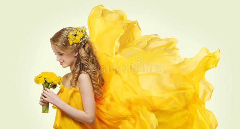 Ung flickaståenden med guling blommar maskrosbuketten royaltyfri foto