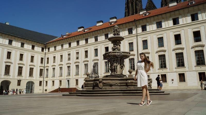 Ung flickastudent som poserar vid springbrunnen på en solig dag i den Prague slotten i Prague royaltyfri bild