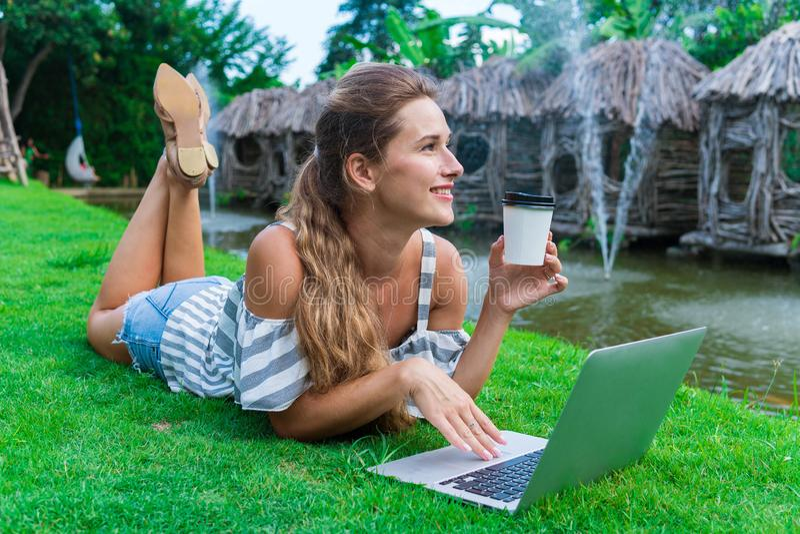 Ung flickastudenten ligger på gräs med bärbara datorn i avbrottet mellan kurser Hon dricker kaffe från papperskoppen arkivfoton