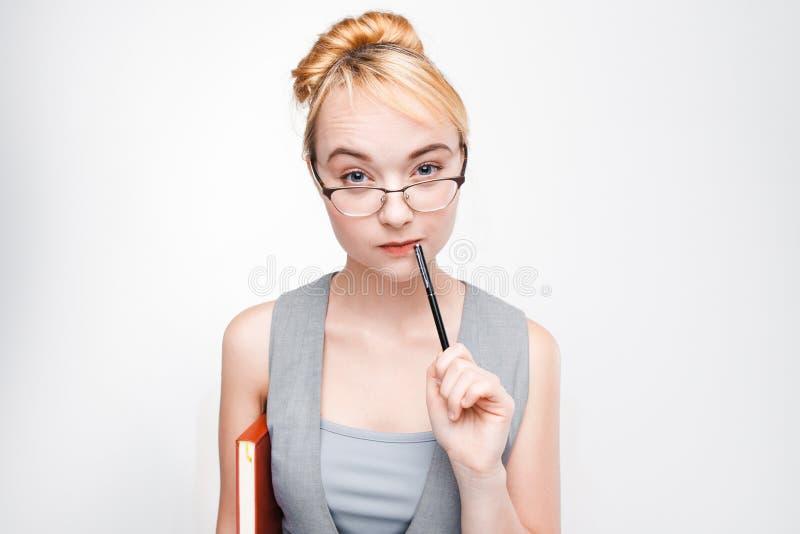 Ung flickastudenten som hårt tänker, skriver nära mun arkivfoto