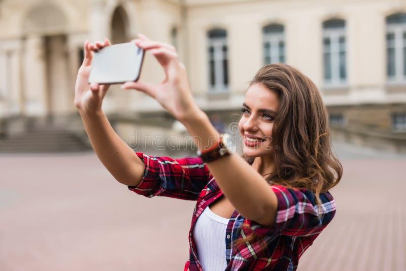 Ung flickatagandeselfie från händer med telefonen på begrepp för stads- liv för sommarstadsgata royaltyfri fotografi