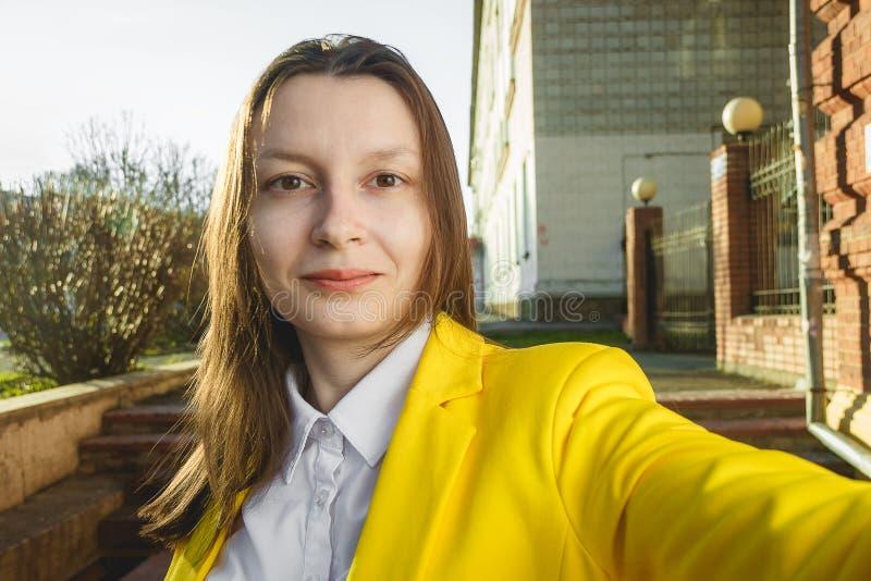Ung flickatagandeselfie från handen på sommarstadsgatan Begrepp för stads- liv royaltyfria foton