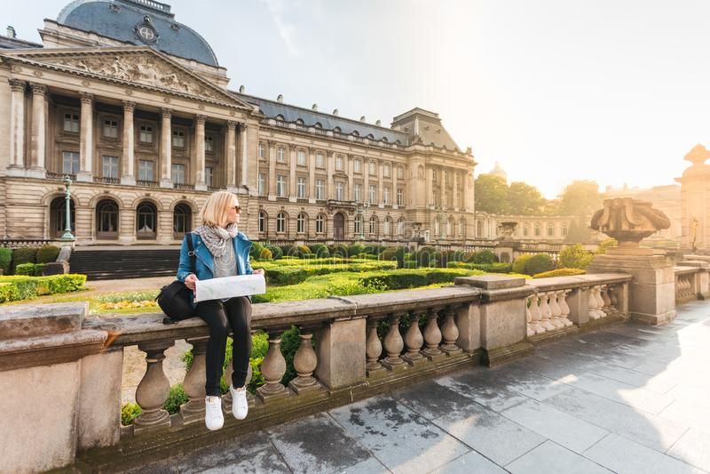 Ung flickaturisten sitter p? bakgrunden av Royal Palace i Bryssel och blickar in i stads?versikten, Belgien arkivbilder