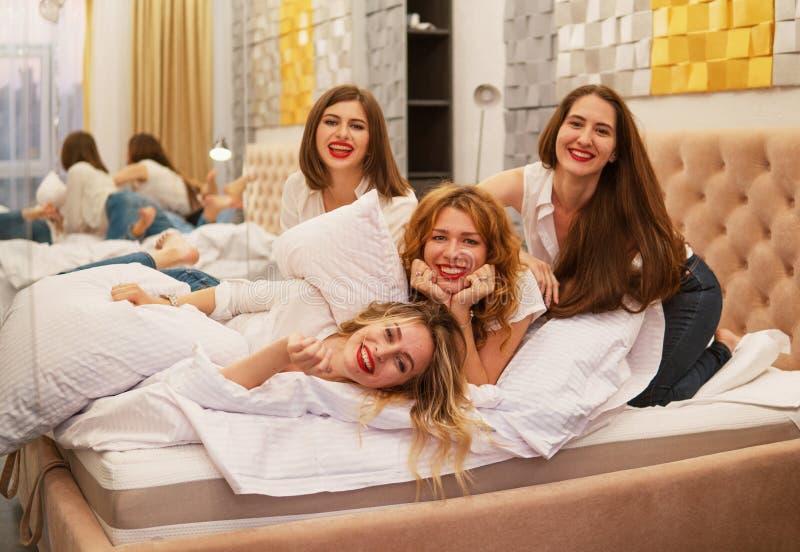 Ung flickavänner som slåss kuddar i sovrummet arkivfoton