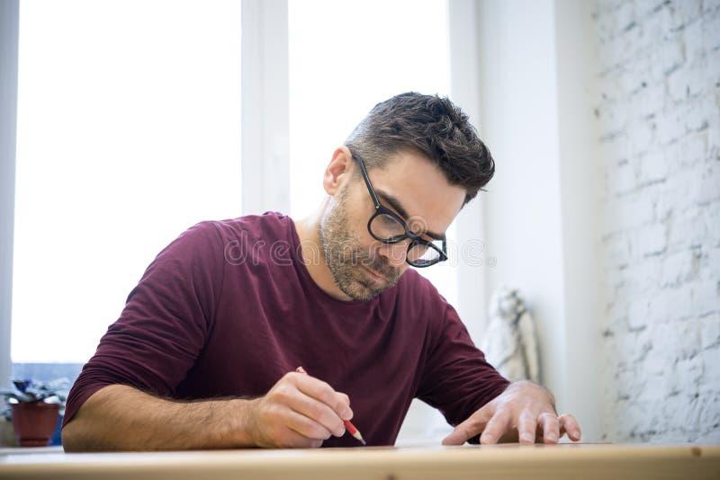 Ung formgivare Drawing skissa genom att använda blyertspennan på trätabellen i ljus studio arkivfoton