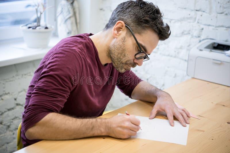 Ung formgivare Drawing skissa genom att använda blyertspennan på trätabellen i ljus studio royaltyfri foto