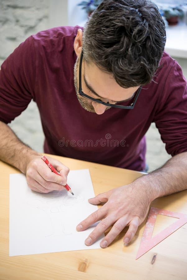 Ung formgivare Drawing skissa genom att använda blyertspennan på trätabellen i ljus studio royaltyfri fotografi