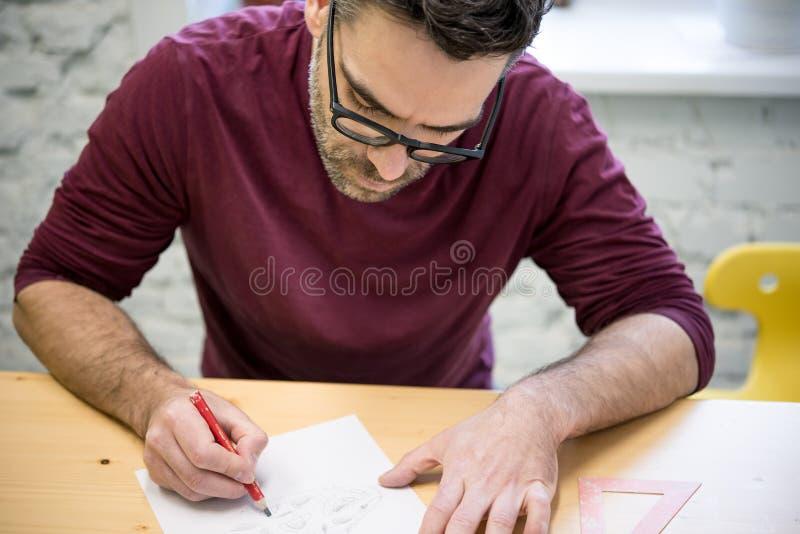 Ung formgivare Drawing skissa genom att använda blyertspennan på trätabellen i ljus studio royaltyfria foton