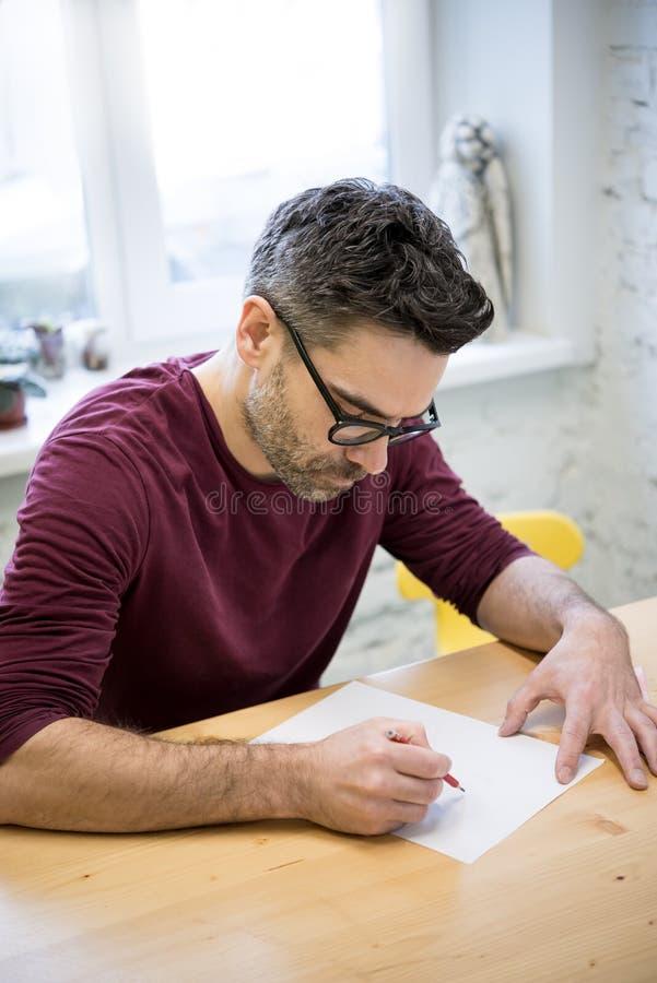 Ung formgivare Drawing skissa genom att använda blyertspennan på trätabellen i ljus studio arkivbilder