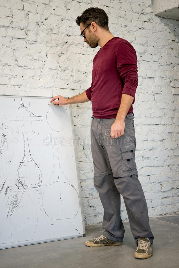 Ung formgivare Drawing skissa på den stora Whiteboarden i den vita studion royaltyfri fotografi