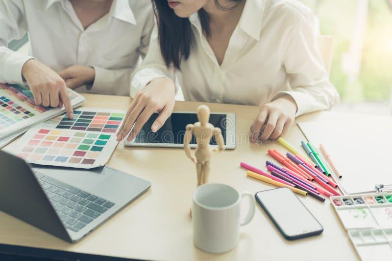 Ung formgivareteamwork som arbetar med färgprövkopior för val på kontorsskrivbordet royaltyfria bilder