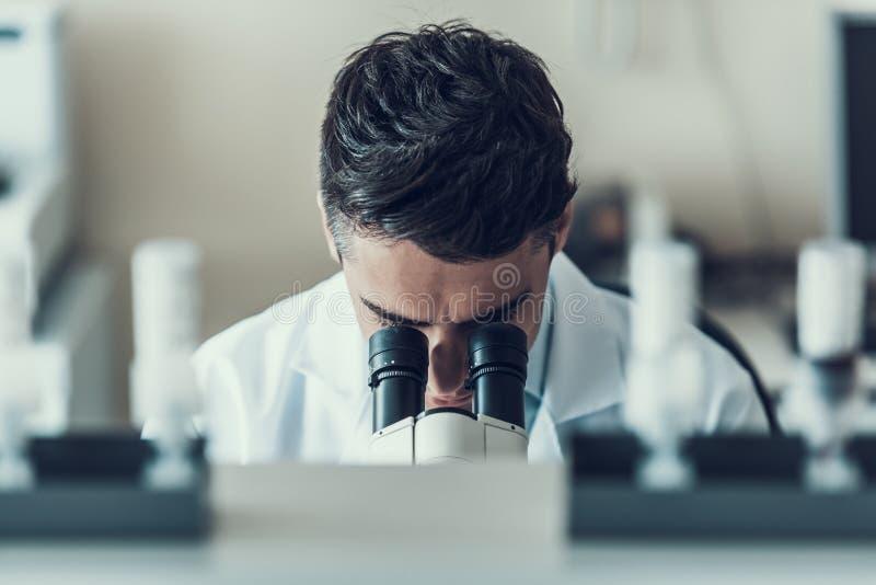 Ung forskare som använder mikroskopet i laboratorium royaltyfri fotografi
