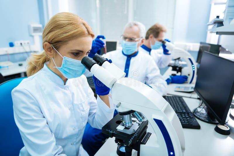 Ung forskare som arbetar med kromosomer arkivfoton