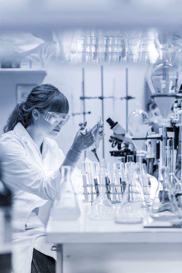 Ung forskare som pipetting i vetenskaperna om olika organismers beskaffenhetlaboratorium arkivfoton