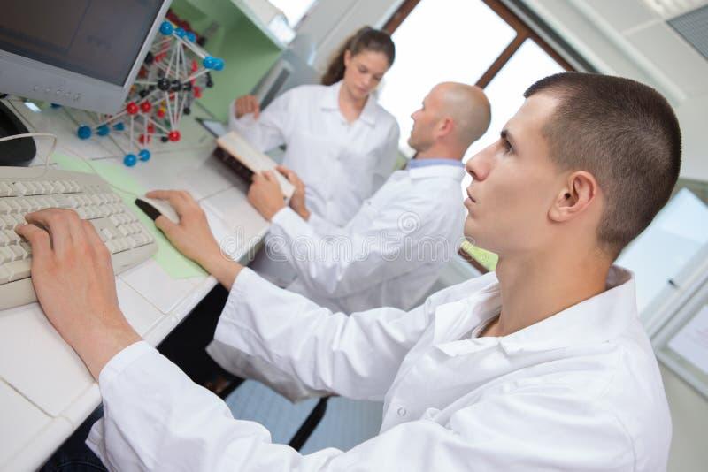 Ung forskare som undersöker dna-modellen i laboratorium royaltyfri foto
