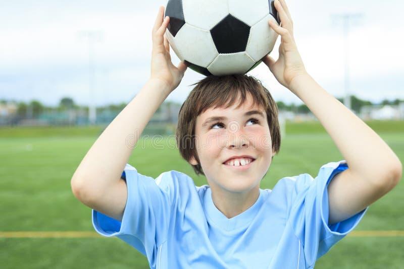 Ung fotbollspelare med bollen på fältet arkivbilder