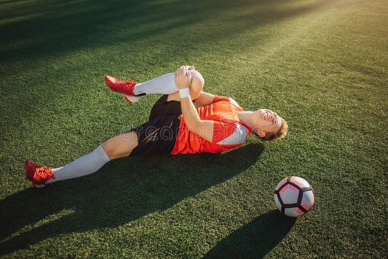 Ung fotbollsspelare som ligger på gräsmatta- och hållbenet Han drar det till honom Grabben känner sig smärtar i knä Boll som ligg royaltyfria foton
