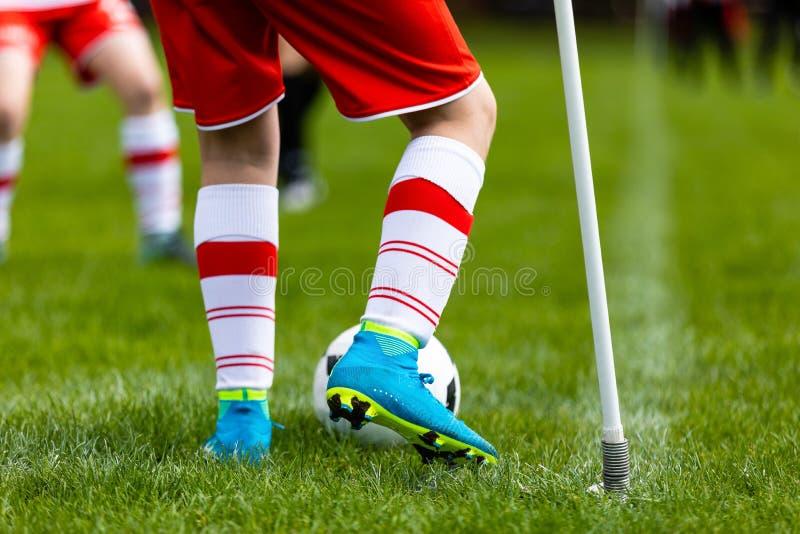 Ung fotbollsspelare som sparkar bollen på fotbollfält Fotbollspelare som sparkar bollen på hörn av fotbollgraden royaltyfri foto