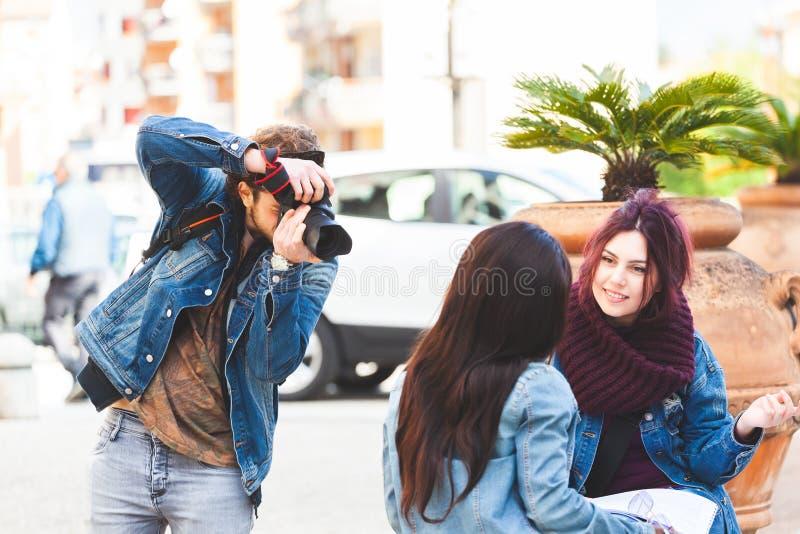 Ung fotograf som tar fotografier av tv? flickor, medan studera royaltyfri foto