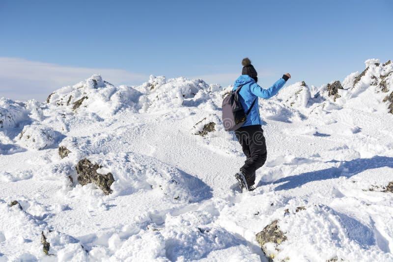 Ung fotvandrarekvinna i det djupa insnöat berget royaltyfria foton