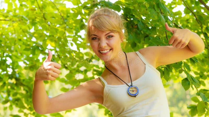 Ung fotvandrarekvinna med kompasset i skog arkivbilder