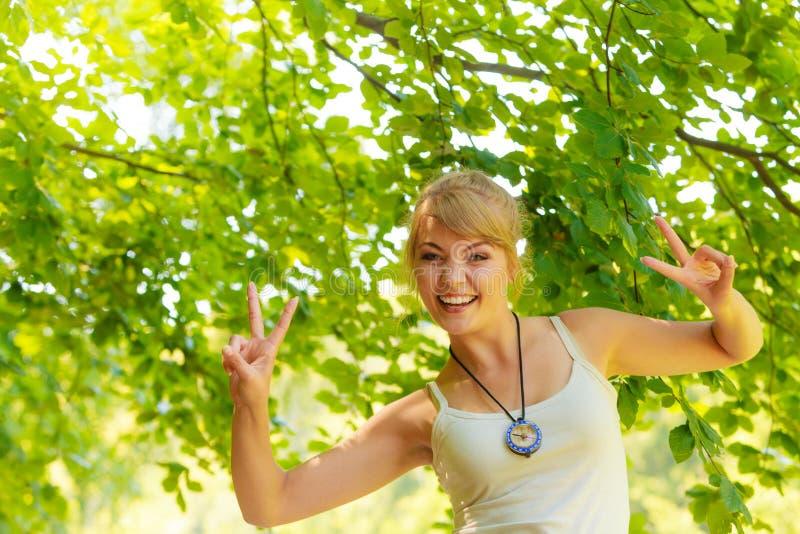 Ung fotvandrarekvinna med kompasset i skog royaltyfria bilder