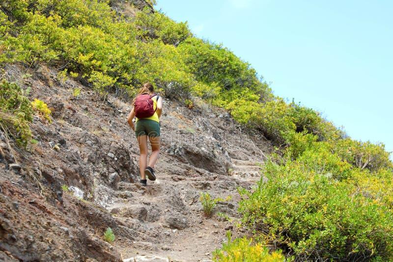 Ung fotvandrarekvinna på hård och stenig slinga i Tenerife arkivbild