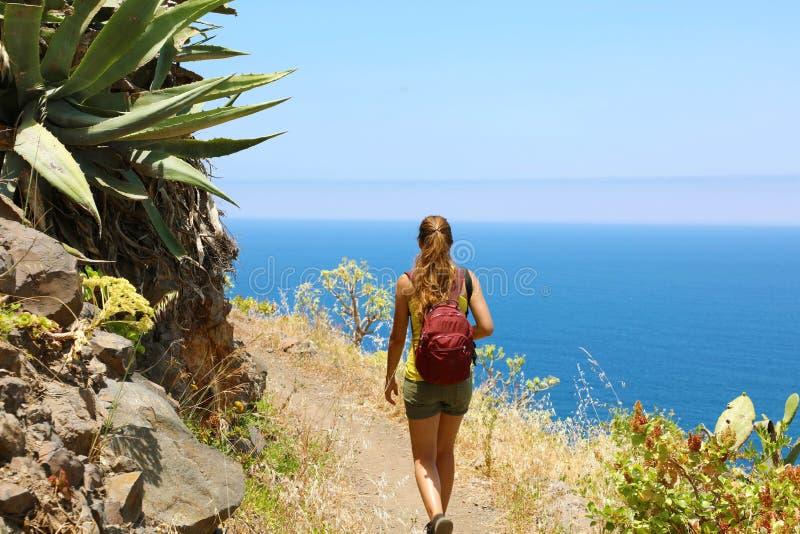 Ung fotvandrarekvinna som går på en slinga som förbiser havet i Tenerife fotografering för bildbyråer