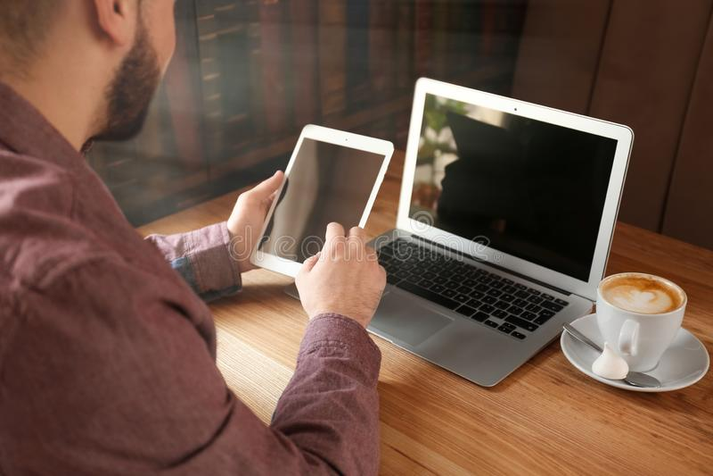 Ung freelancer med minnestavlaPC och bärbar datorarbete i kafé royaltyfria foton